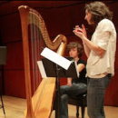 Photo of instructor with student at harp